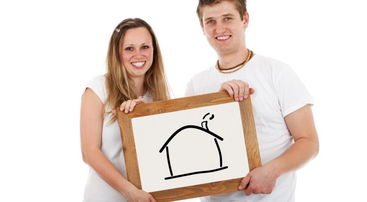 image of couple holding a picture of a house
